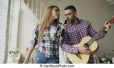Funny happy and loving couple dance singing with tv controller and playing guitar. Man and woman have fun during their holiday at home
