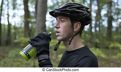 Biker Drinks Water from Bottle - Closeup shot of young...