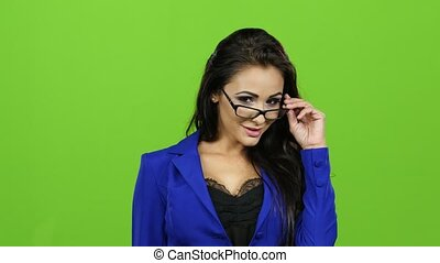 Sexy brunette woman with glasses posing on camera, green...