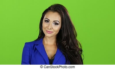 Brunette girl in blue jacket posing on camera, green screen