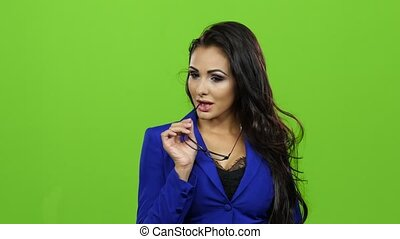Seductive brunette woman in glasses posing on green screen...