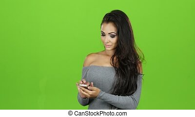 Brunette woman with smile plays on mobile, green screen...