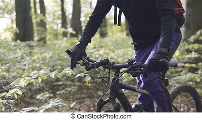 Biker in the Forest - Young sports man riding bicycle on the...