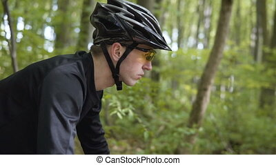 Man Rides Bicycle in the Forest - Closeup shot of young...