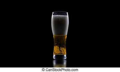 A glass of beer on a black background