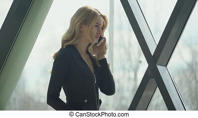 Beautisul blonde girl in black standing by the window and talking on the phone.