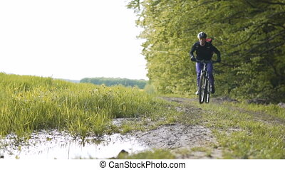 Backpacked Man Rides Bicycle in the Forest Puddle Pool -...