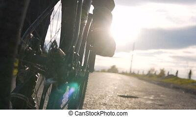 Biker Against Sunset - Man rides a bike on the asphalt road...
