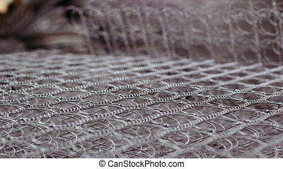 Worker manufacturing mattress in factory