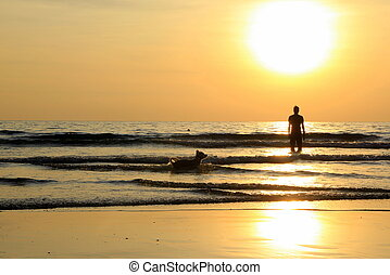Travel to island Koh Chang, Thailand. A man with a dog on the sunset beach.