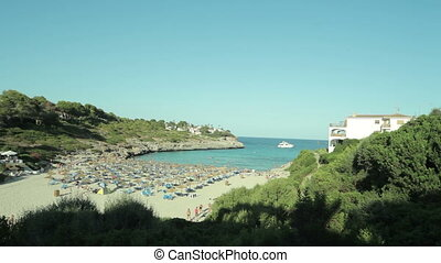 People bathe and rest on the beach. Spanish beaches in Cala Mendia. Mallorca