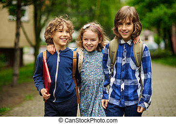 Three little school students, two boys and the girl, stand...