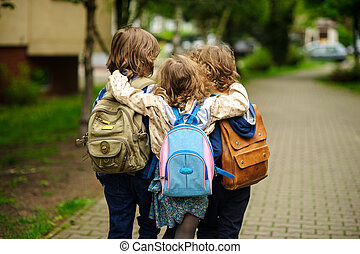 Three little school students go in an embrace to school....
