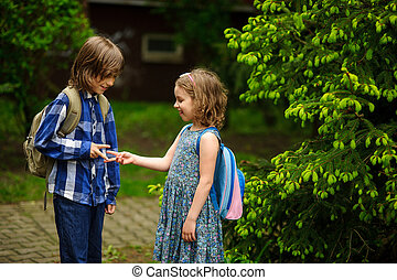 Two little school students, the boy and the girl, cheerfully...