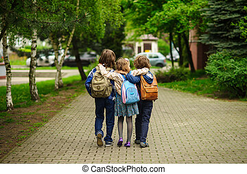 Three little school students, two boys and the girl, go in...