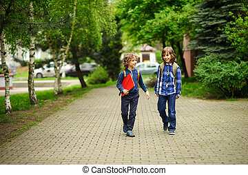 Elementary school students hurry to school. Schoolboys with...