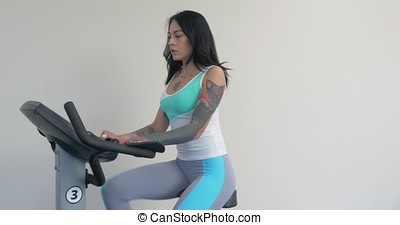Three beautiful young women working out on bikes at the gym. Active young woman working out on exercise bike stationary bicycle. Sporty girl training at fitness hall, gym. Girl on Exercise bike, bicycle