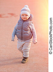 Toddler child in warm vest jacket outdoors. Baby boy at...