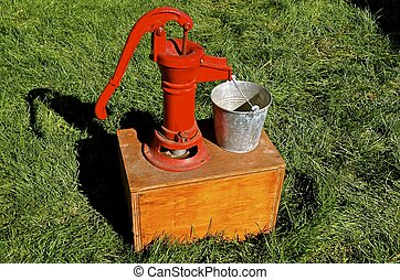 Restored hand water pump - A restored red hand pump is used...
