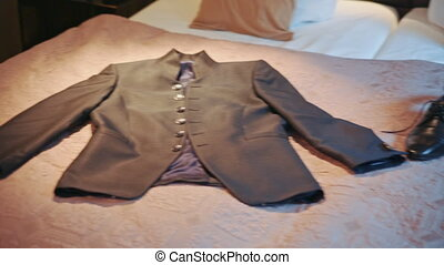 men's jacket lying on the bed.