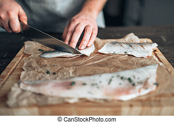 Chef cuts raw fish slices on wooden cutting board - Male...