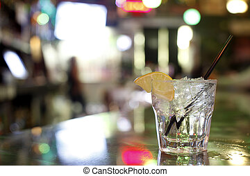 A gin and tonic on the counter of a bar.