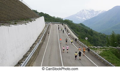 big group of runners running down road mountain marathon...