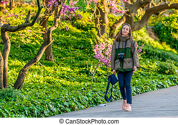 Woman walking along park trail in spring day. Barcelona, Catalonia.