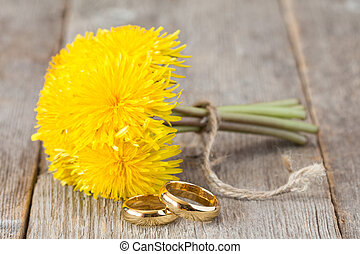 Wedding rings and bunch of yellow dandelion flowers on...