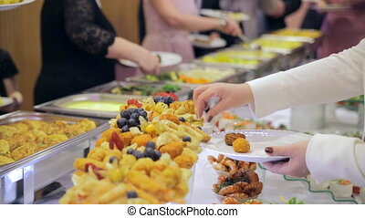 Restaurant guests select food from a buffet.