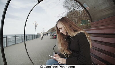 Woman with white smartphone on the bench on the boardwalk...