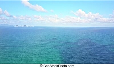 Drone Flies over Azure Ocean against Blue Sky with White Clouds