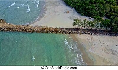 Drone Flies from Azure Sea Close to Sand Beach with Pier