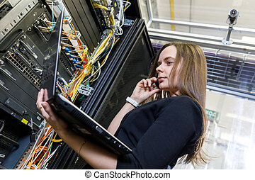 Young woman engineer at the network equipment - Young woman...