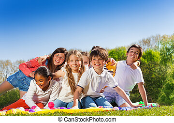 Happy kids sitting on the lawn in summer park