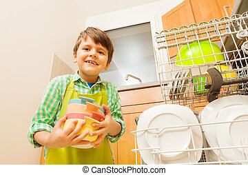 Happy kid boy loading dirty dishes to dishwasher - Portrait...