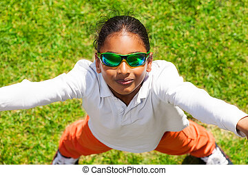 African boy in sunglasses standing on green lawn