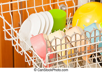 Opened dishwasher with clean utensils on its rack - Close-up...