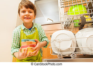 Boy holding bowls standing next to the dishwasher - Happy...