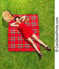 Beautiful girl in red dress relaxing on the picnic