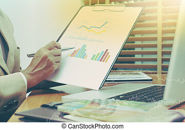 Business woman analyzing graph document with financial...