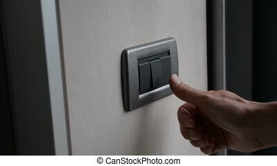 Hand turning on and off light switch - Male hand turning on...