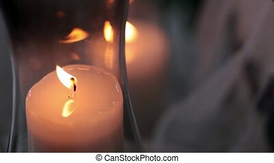 lit candle in a vase in a dark room