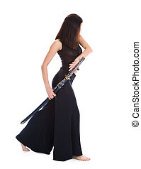 Beautiful woman in an aggressive posture with a sword katana...