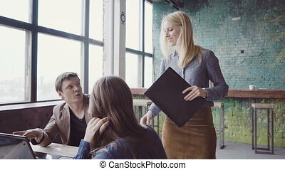 Young blonde team leader walking through modern office and controls work of employee. Female looks the fabric examples.