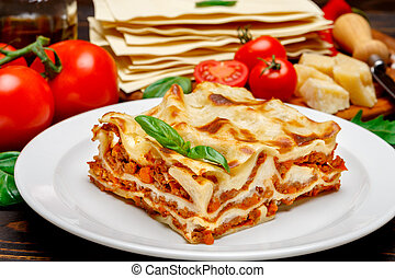 Portion of tasty lasagna on wooden backgound - Portion of...