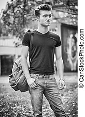Young man standing in city environment, with backsack