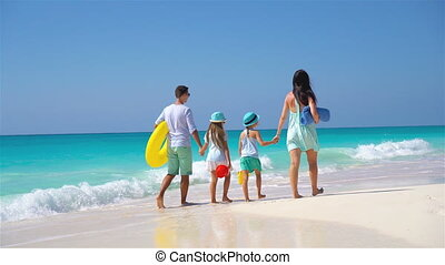 Family beach vacation - Young family of four on beach...