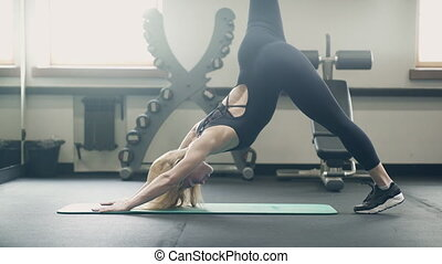 Woman doing exercise for leg standing on arms mat in fitness...