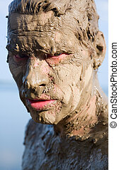Man's face is very dirty in the mud. Dirt is not curative